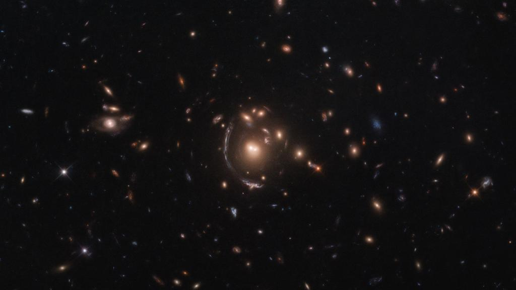 In this #HubbleFriday image, the galaxy LRG-3-817 appears as a long arc, left of the central galaxy cluster. It looks warped due to gravitational lensing, which happens when a huge distribution of matter sits between Earth and a distant source of light: