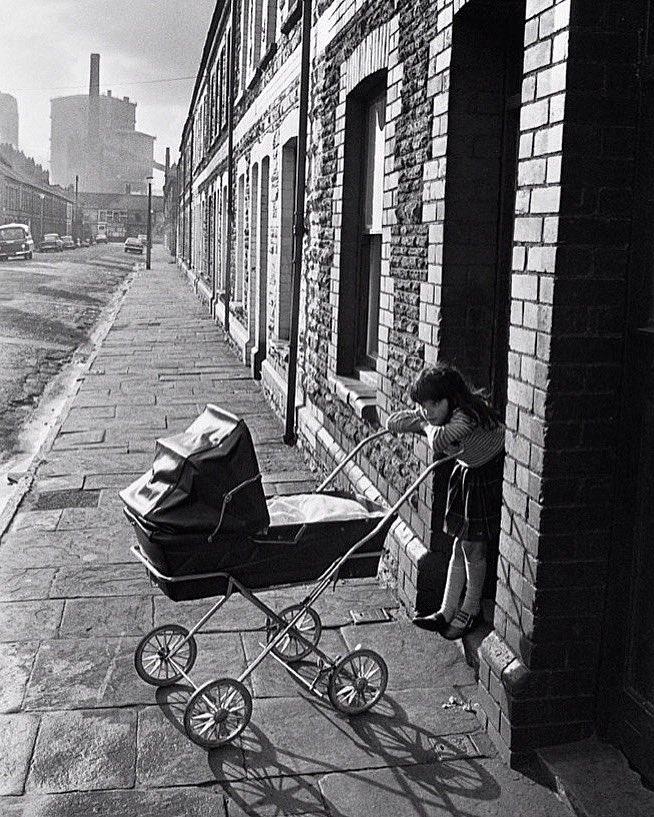 A girl minding a baby on her doorstep. Splott, Cardiff, 1974. Photo © Robin Weaver.