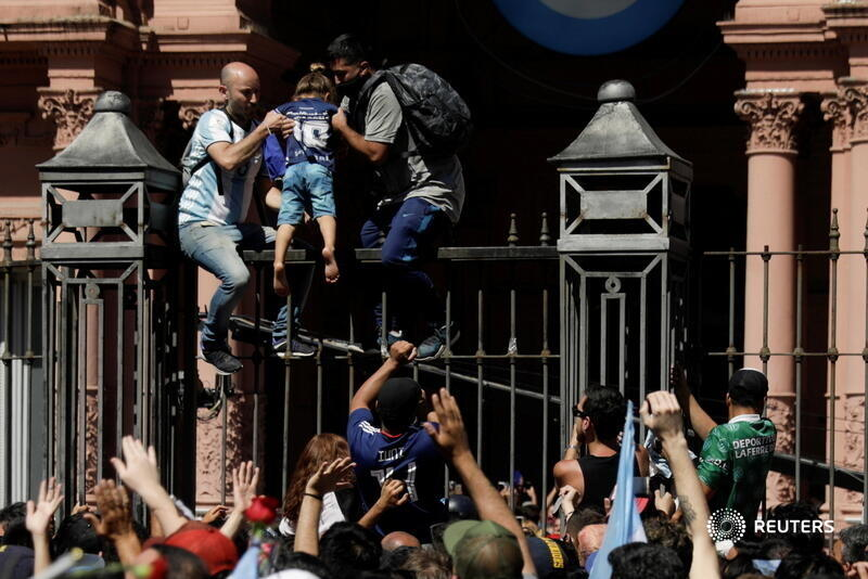 Men help a child climb on the fence of the Casa Rosada presidential palace as people gather to mourn the death of soccer legend Diego Armando Maradona, in Buenos Aires, Argentina. More photos of the day: https://t.co/6Z3pnCA2Mb 📷 @RicardoMoraesRM https://t.co/wKGPsVKXbx
