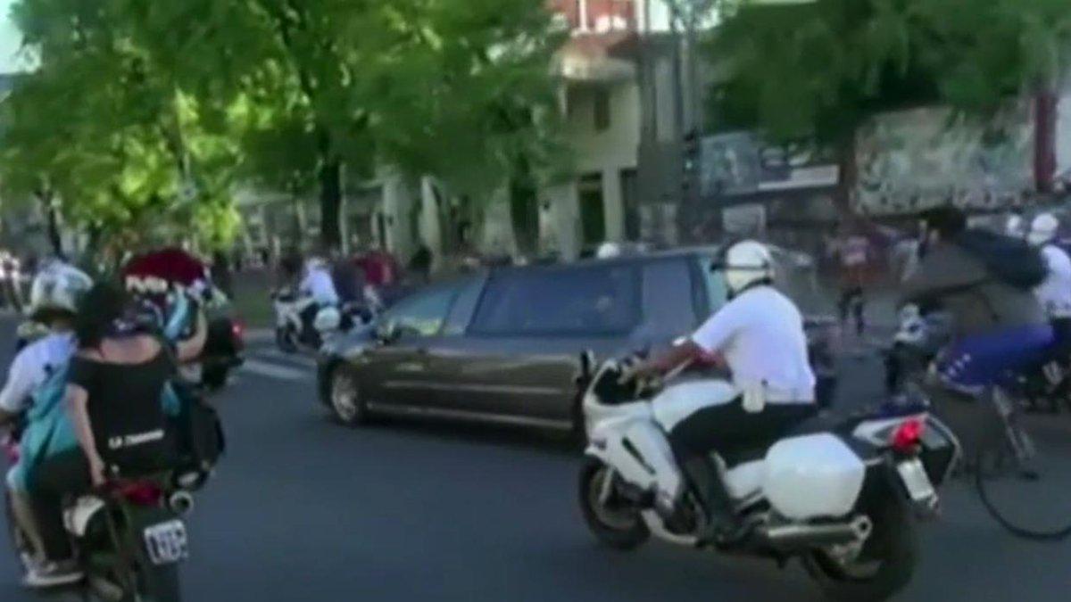 Cientos de personas siguen en motocicleta y bicicleta el cortejo fúnebre con los restos de Maradona.