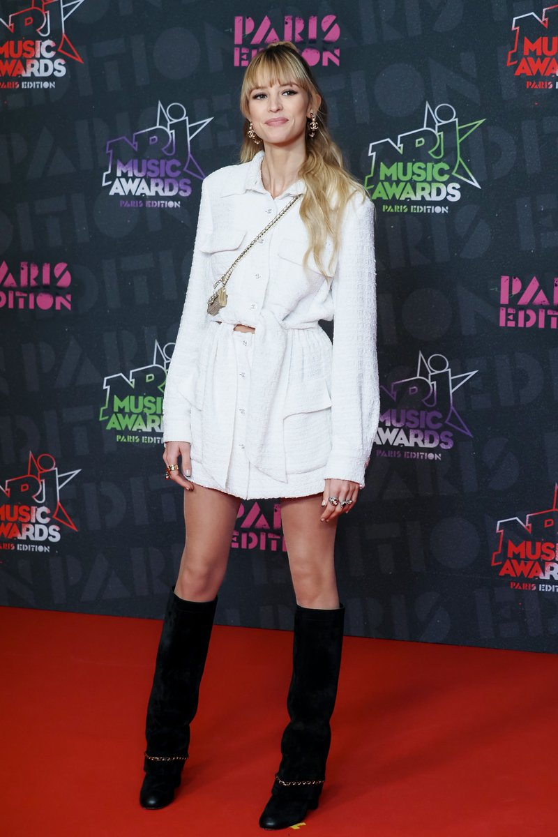 "Artist and House ambassador Angèle presented the award for ""Best International Female Artist"" in a white tweed dress from the Cruise 2020/21 collection, at the 22nd ceremony of the NRJ Music Awards in Paris. #CHANEL #CHANELCruise #CHANELMakeup"