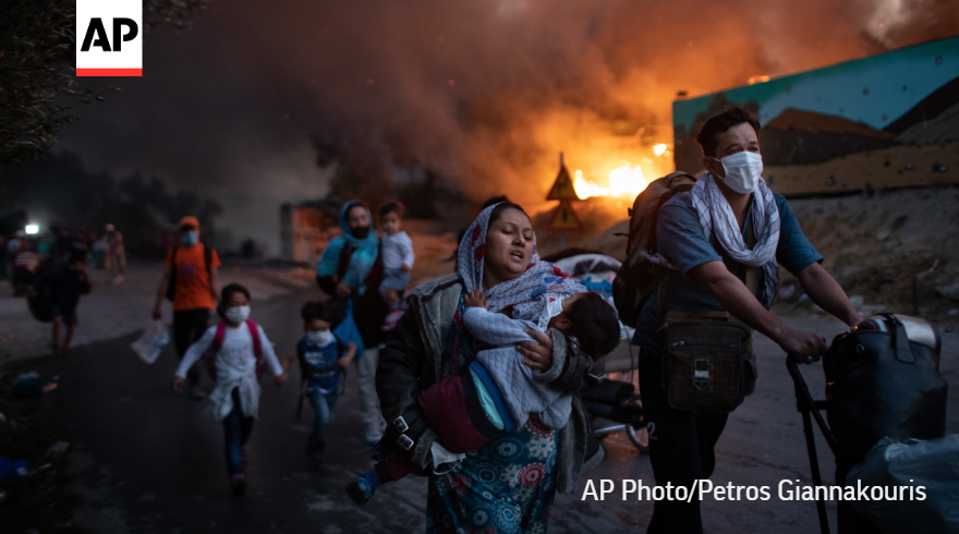 This is the world that @AP photographers captured in 2020, a world beset by every sort of catastrophe.  In this @PGiannakouris photo, migrants flee from a fire at the overcrowded Moria refugee camp on the island of Lesbos, Greece.  SEE MORE:   #APPhotos2020