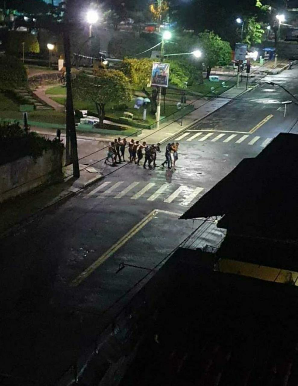 Fotos de um grupo de pessoas que seriam reféns andando próximo à uma praça