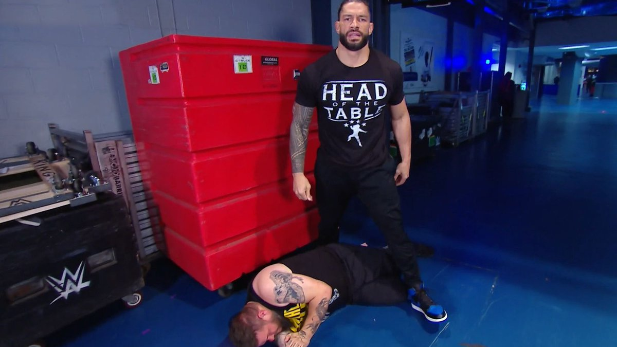 Roman Reigns stands over Kevin Owens.