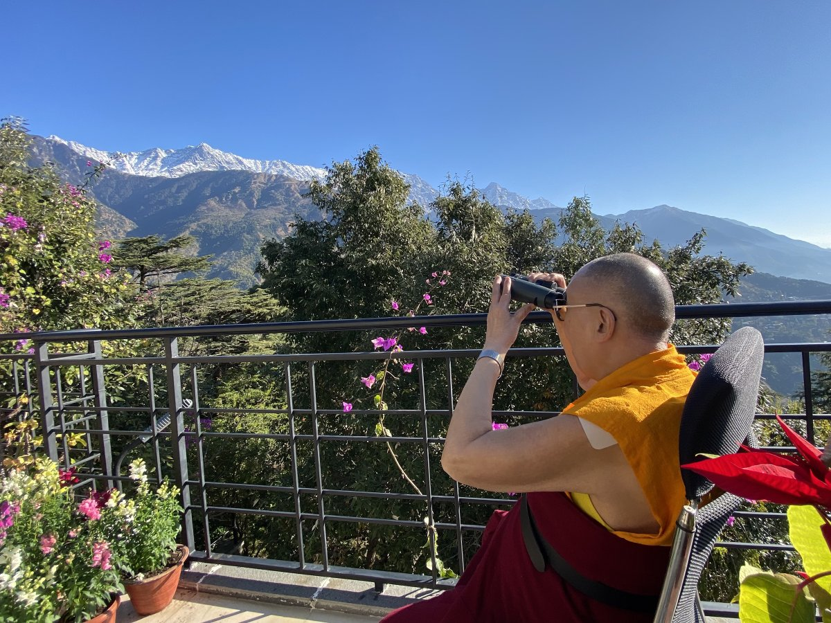 Under a bright blue sky HHDL trains his binoculars on the snow-capped peaks behind his residence in Dharamsala, HP, India on December 19, 2020. (Photo by Tenzin Jamphel)