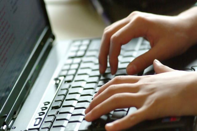 Imagem em close das mãos de pessoa digitando no teclado de um notebook