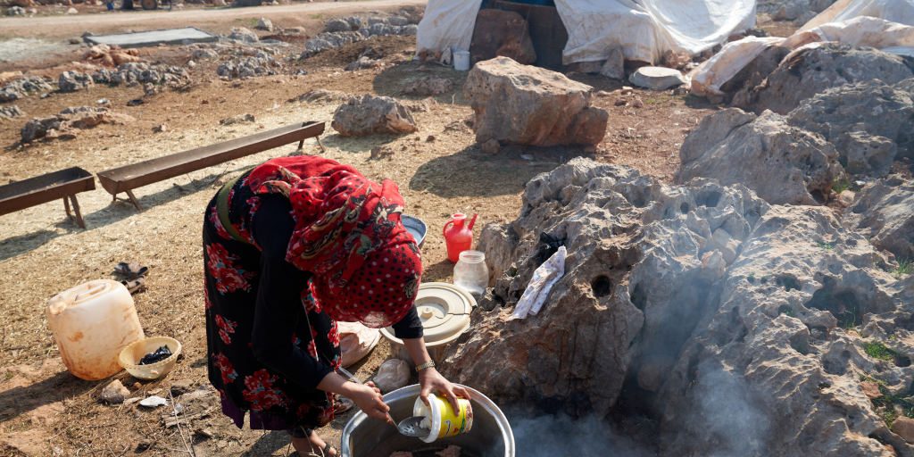 Yara*, 12, helps her mother cook near their tent in a camp in #Syria. DEC charity @WorldVision is working with local partners to help people displaced due to war protect themselves against Covid-19 by providing hygiene kits and other services. Please help: