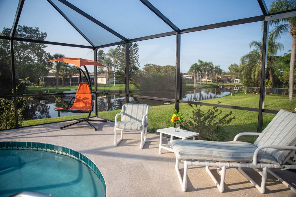 Lounge areas by the pool with canal in the background  waterfront vacation home, sunny vacation rentals, romantic getaway, quite getaway in Rotonda West  #relaxingvacationrental #MondayMorning  #holidays #getaway #vacations #waytooearly #NJWK15 #Mondayof2021  #vacationmode