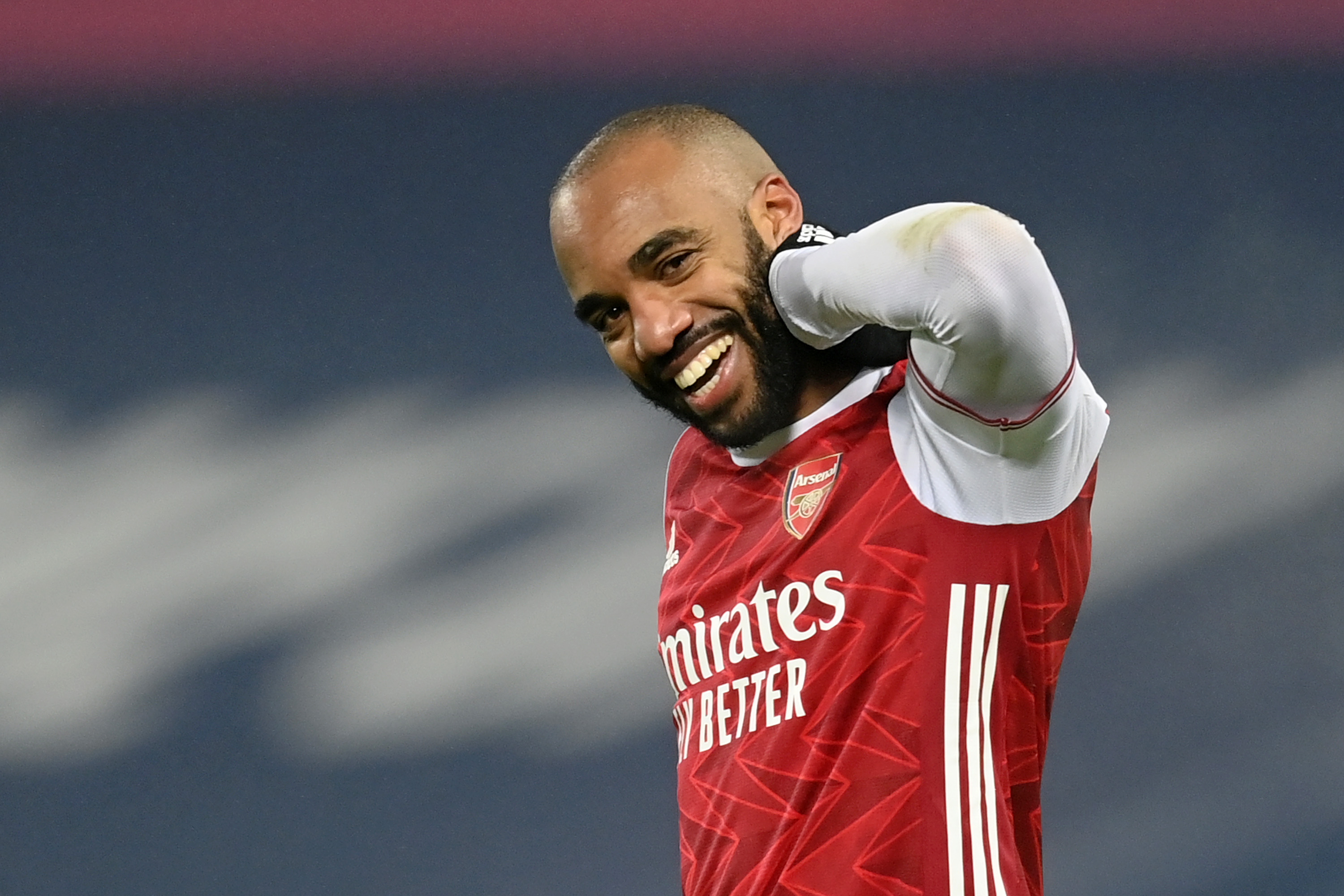 Alex Lacazette smiles at the camera as he rubs his neck