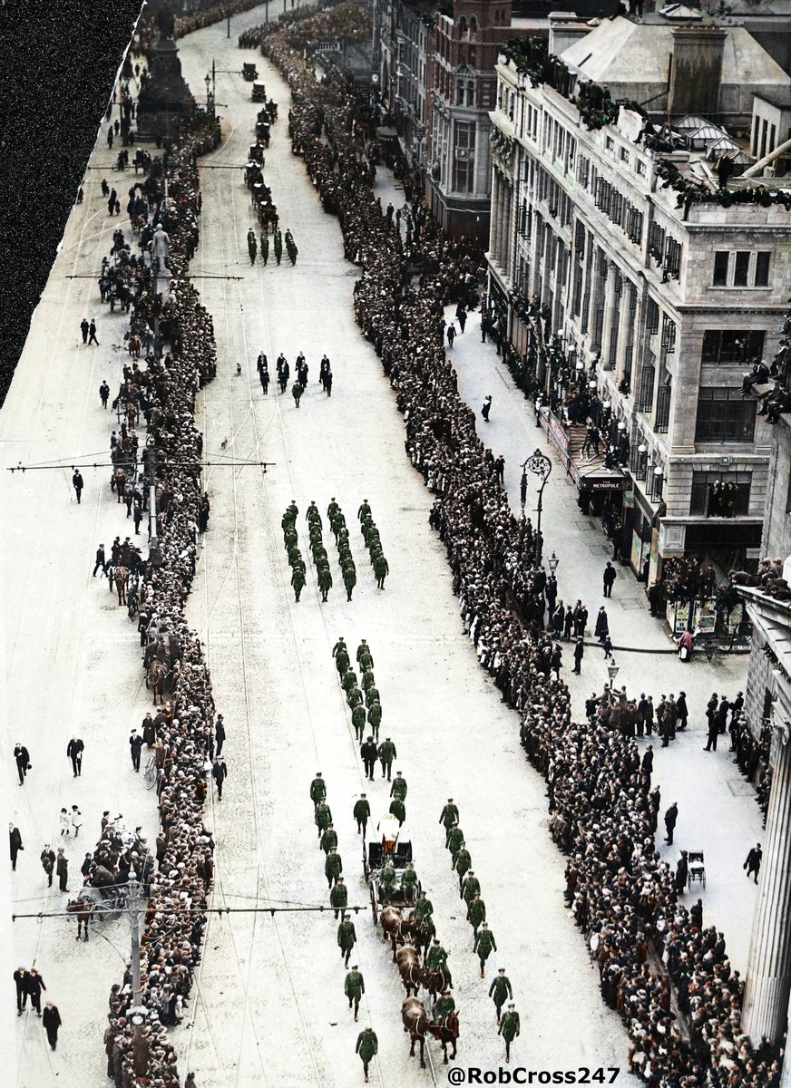 Bringing #Ireland's History to Life.🇮🇪🌹 My colourised photo of the impressive scenes from the funeral of Michael Collins on August 22nd, 1922 passing the G.P.O. as seen from Nelson's Pillar on O'Connell Street which includes people sitting on the roof of the General Post Office.