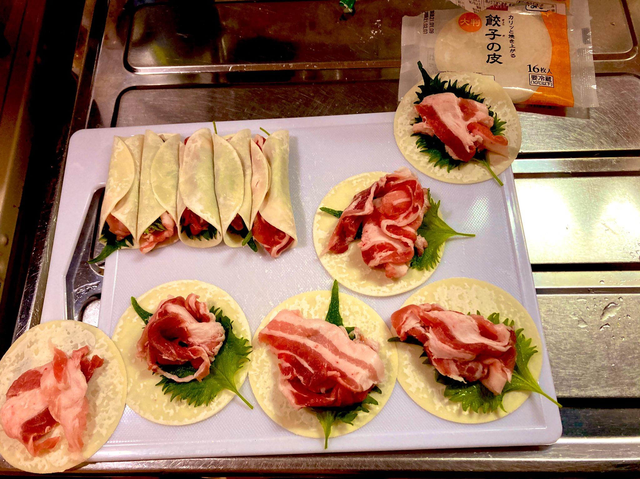 餃子の皮で紫蘇と豚小間を包む作業