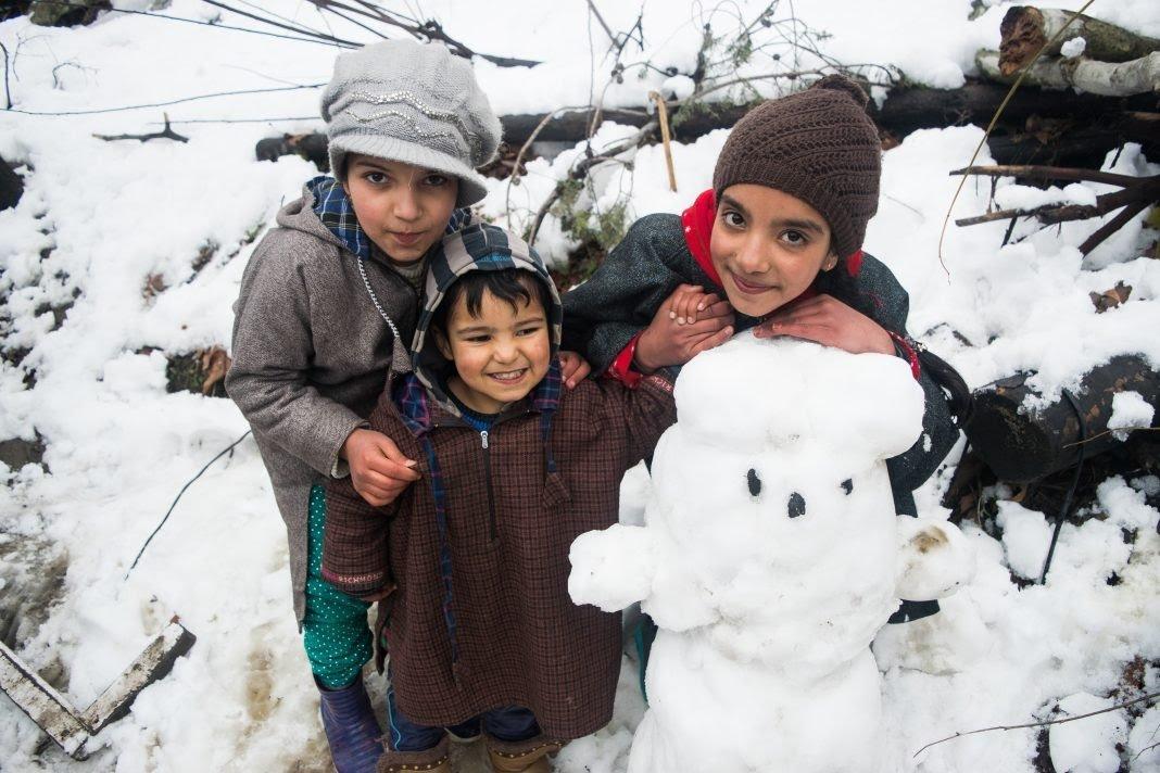 Kashmiri kids pose beside their snowman, #Kashmir #winter #childhoodmemories