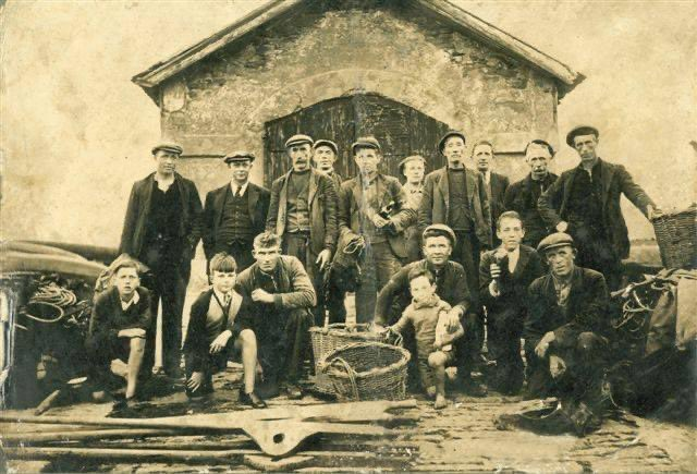 Some locals relaxing outside the Kilkee Boathouse in 1910. The boathouse hasn't changed one bit! Contact  for reservations. #Kilkee #loophead #wildatlanticway #atlanticocean #cliffwalk #CountyClare #beach #surf #seafood #summer #pollockholes #boutiquehotel