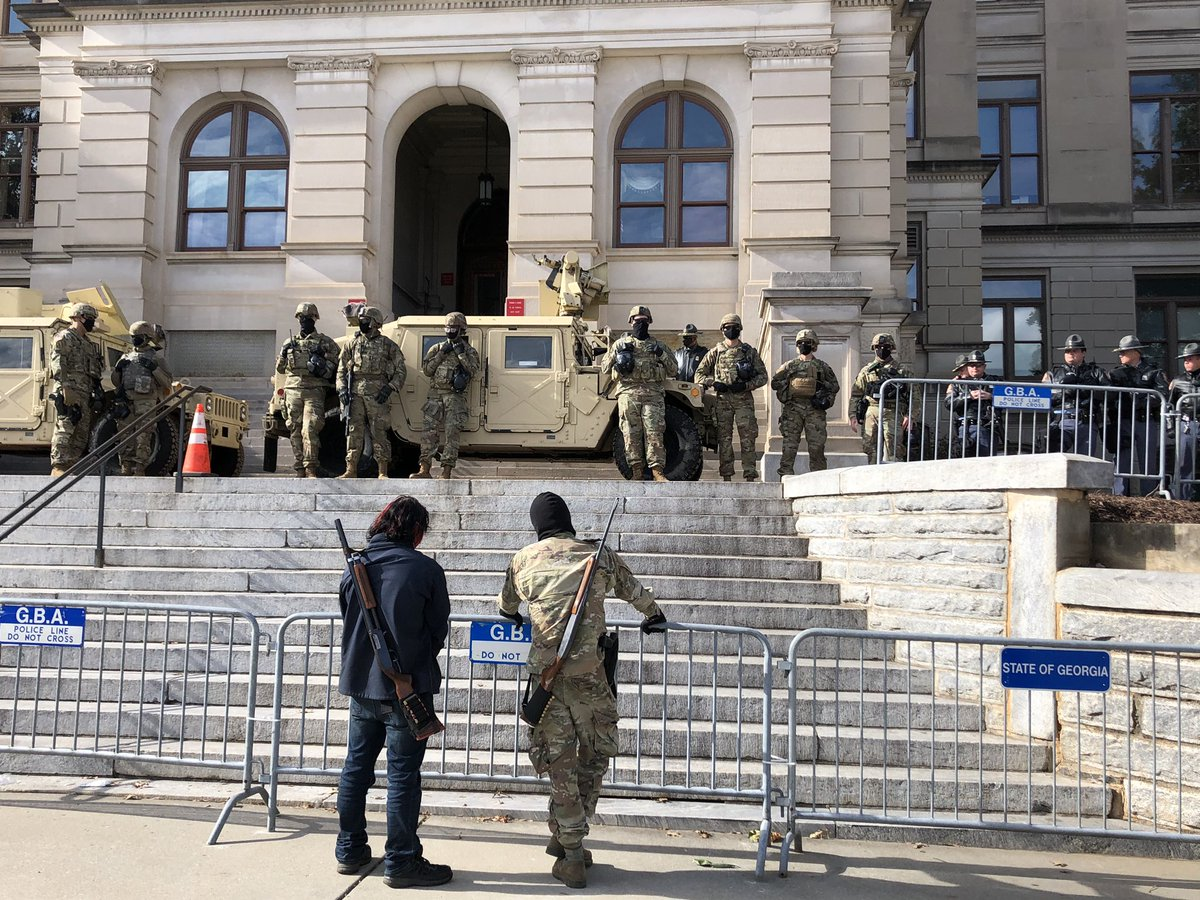 National Guard members and Georgia State Troopers are just staring at the two armed protestors.
