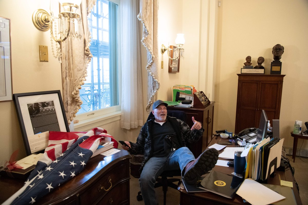 A man who breached Capitol security sits at the desk of House Speaker Nancy Pelosi. (Photo: Saul Loeb/Getty)