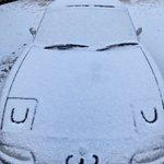 車のボンネットに積もった雪で作ったかわいい顔!