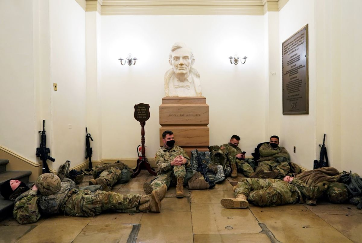 One week after insurrection at US Capitol, National Guard members sleep under plaque dedicated to troops who were quartered in the Capitol in response to Pres. Lincoln's call for volunteers during the Civil War.  📷 Joshua Roberts/Reuters (left) / Architect of the Capitol (right)