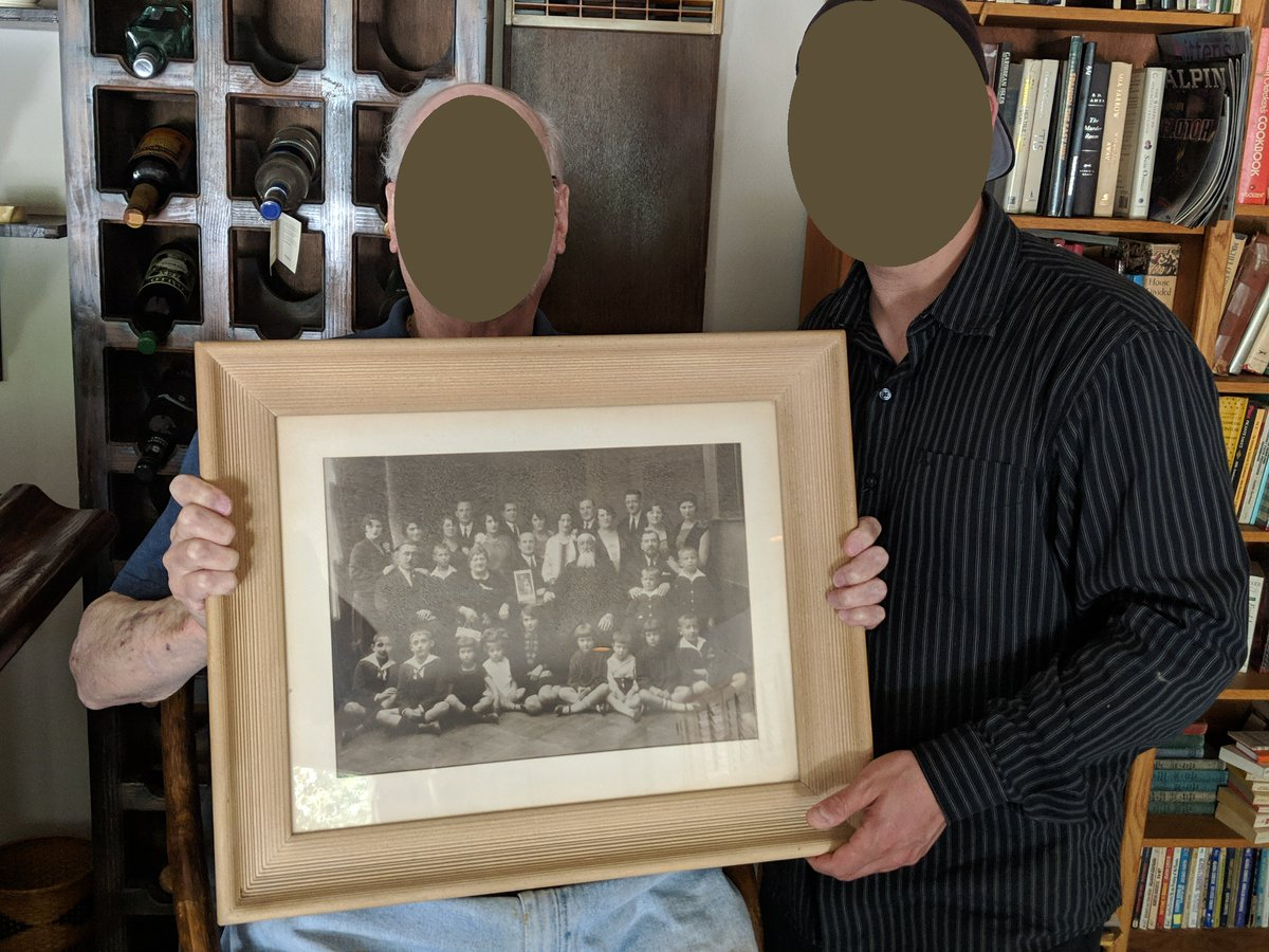 Here's me with my dad, back in pre-pandemic 2019 when we last were able to see one another. He's holding a photograph that hung on the wall of my grandmother's bedroom. It's a photo of my grandfather with his family back in Poland, just before the start of WW2.