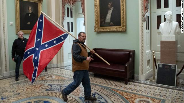 Authorities have arrested the man photographed holding a Confederate flag during last week's Capitol siege, according to a law enforcement official