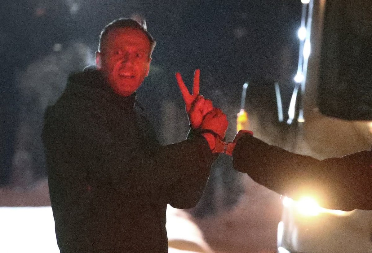 Navalny flashes a V sign to chanting supporters as he is marched from a police station to a van that will drive him to prison. He's called for protests on Saturday. Expect to see a lot of this. (pic via @tass_agency)
