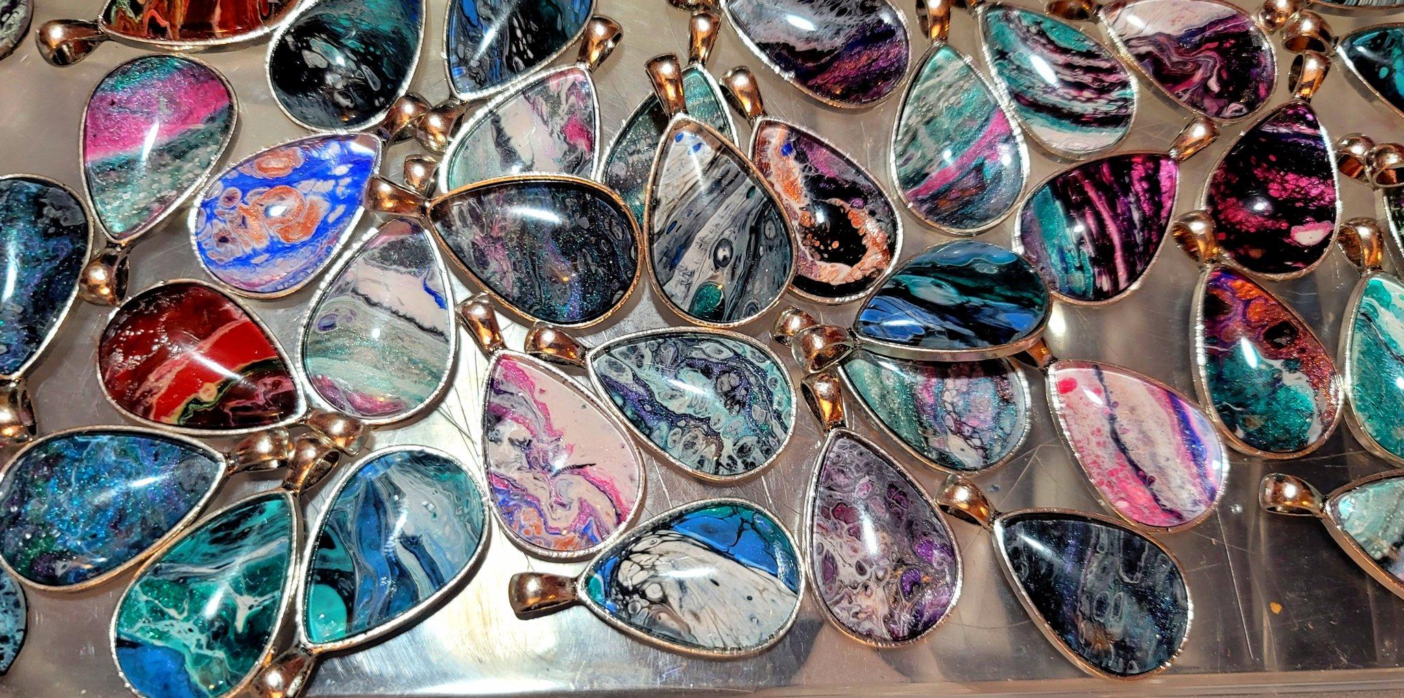 A few dozen teardrop pendants with acrylic pour designs