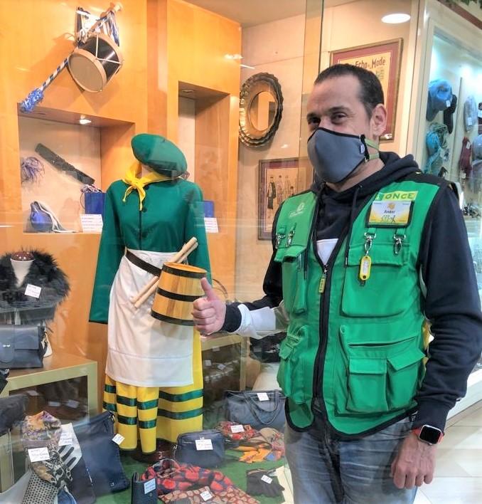 Ander Miranda ataviado con el chaleco verde y antifaz, posa tras su jornada laboral en el escaparate de la boutique Jospehine al lado del maniquí que exhibe el traje de aguadora de Hamaika Danborrada