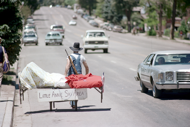 Aspen, Colorado July 1980  Main Street, 4th of July  Photograph by Nick DeWolf   #photography #film #color #35mm #aspen #colorado #mainstreet #people #parade #man #rifle #hospitalbed #streetphotography #4thofjuly #1980s