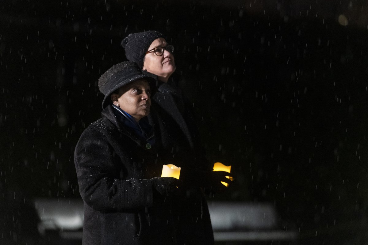 .@chicagosmayor, left, and First Lady Amy Eshleman stand together in Millennium Park, with candles in hand, looking at a partially darkened skyline during a national COVID-19 memorial.  #Chicago #COVIDMemorial