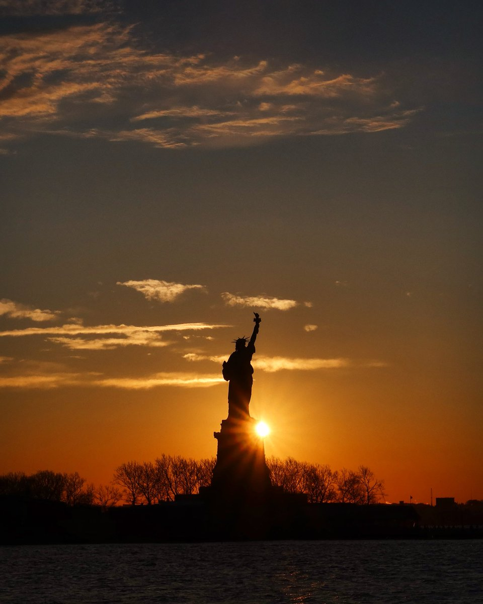 The sun rises behind the Statue of Liberty in New York City as the United States wakes up today with a new President in the White House #newyork #newyorkcity #NYC @statueellisnps @agreatbigcity #sunrise #statueofliberty