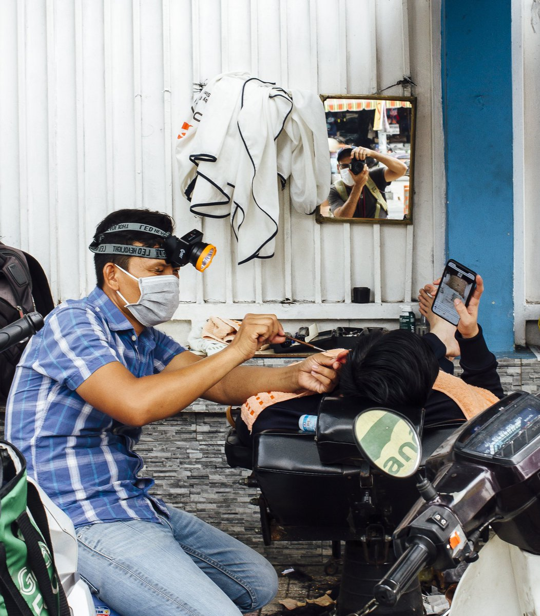 A customer looks at his phone as a street barber cleans his ear. Can you spot me in the mirror?  #photographer #Vietnam #selfie #Travel #Vietnam #Saigon #Saigoneer #photojournalism