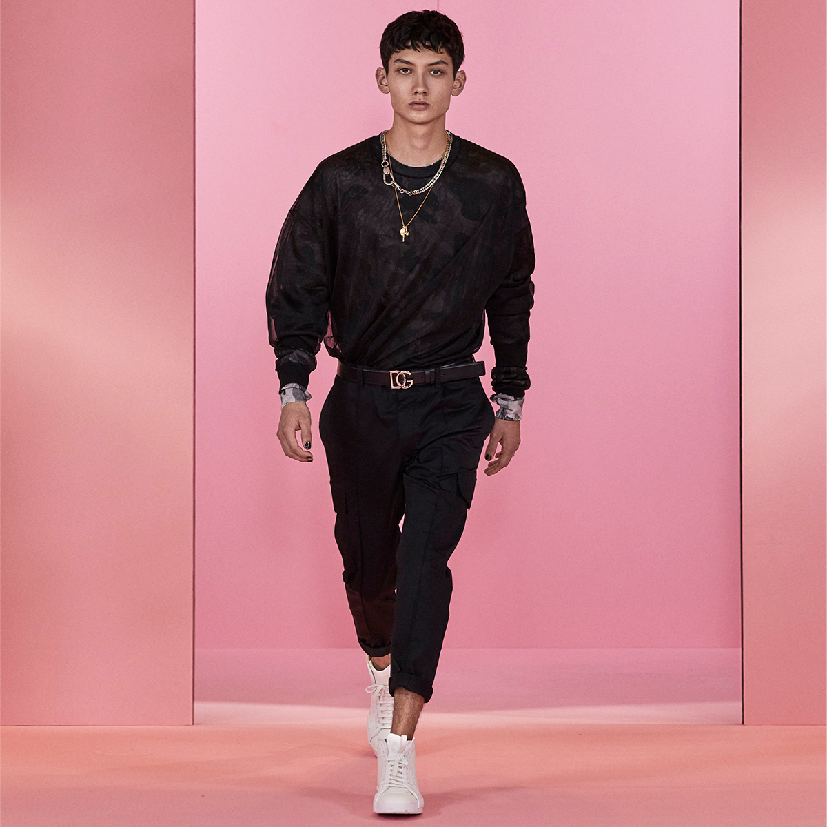 The #DGDigitalShowMan1 look is made up of transparent black and camouflage shirts, black trousers, a #DolceGabbana logo belt and white high-top sneakers.  Shop the DNA look at the link:  #DolceGabbana