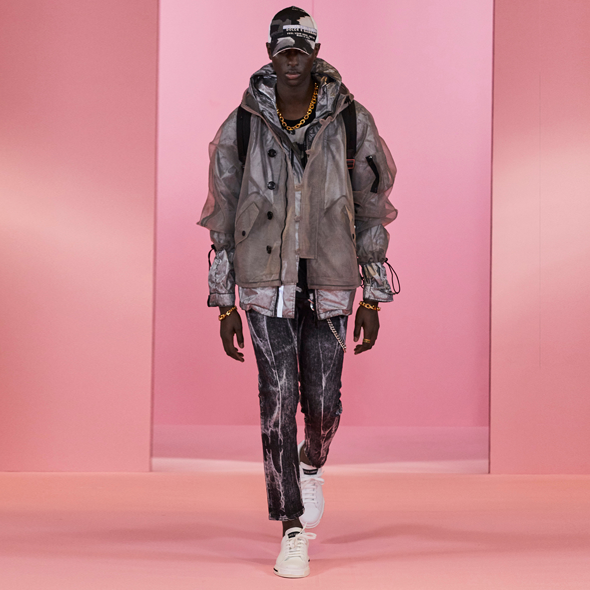 The #DGDigitalShowMan1 look features a nylon jacket with a hood and a patch embellishment, marbled jeans, white sneakers and a camouflage cap.  Shop the DNA look at the link:  #DolceGabbana