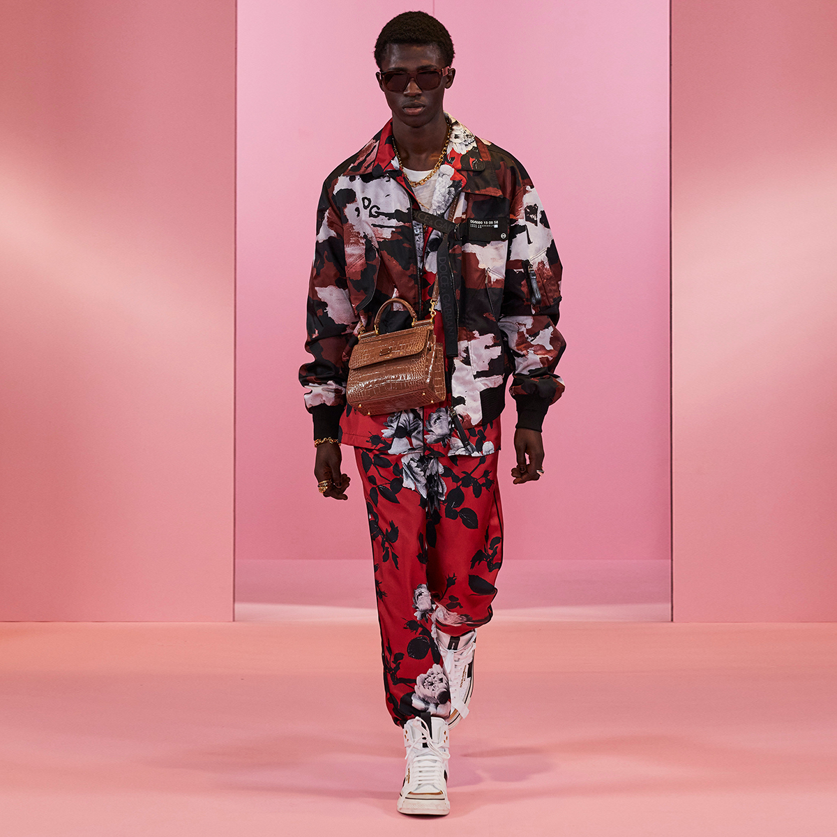 The #DGDigitalShowMan1 look is made up of a camouflage jacket over a floral-printed red pyjama set, white high-top sneakers, a brown #DGSicilyBag and #DGEyewear.  Shop the DNA look at the link:  #DolceGabbana