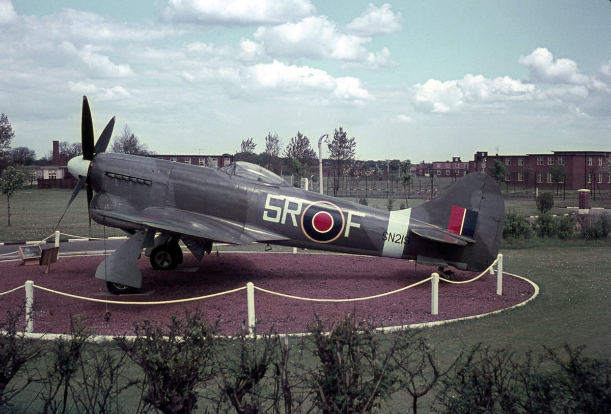Now, that's what I call a Gate Guardian!😎 This was the sight greeting visitors to RAF Middleton St George (now Teesside Airport) in 1962. The Hawker Tempest was built from parts by @33SqnRAF, then based there.  It's now at @RAFMUSEUM Hendon, painted as a TT5.  Photo- Jim Cain.