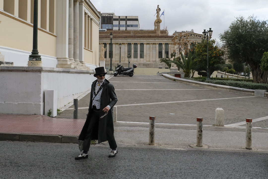 A man wearing a #tophat and a #mask to prevent the spread of #COVID19 walks in #Athens, #Greece, Friday, Jan. 22, 2021. (Photo/Michael Varaklas)