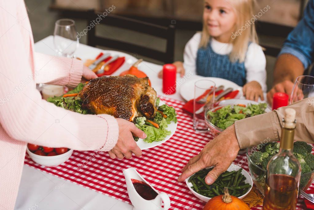 Cropped view of mother holding plate with turkey. Photo by AndrewLozovyi #Thanksgiving #Family