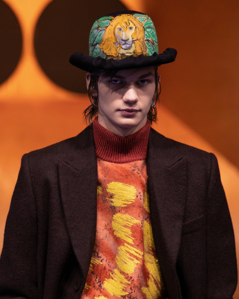 At the unveiling of #DiorWinter21 by Kim Jones , contrasting pops of intense color, brushstrokes reborn as knitwear motifs and a hat painted with the likeness of a lion all highlight the singular aesthetic of collaborative artist Peter Doig.