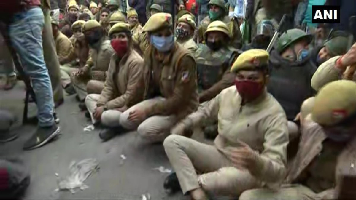 Delhi: Police officials sit on road in Nangloi to block the area where farmers holding tractor parade have reached