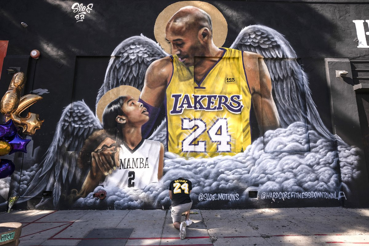 A fan kneels at a Los Angeles mural of Kobe Bryant and his daughter, Gianna, on the one year anniversary of their deaths.  📷 Jae C. Hong / AP