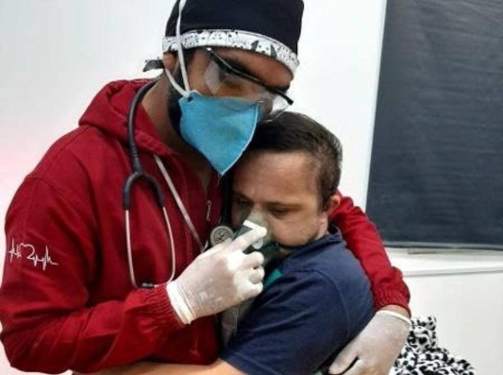 Foto de enfermeiro que abraça paciente com síndrome de Down para dar oxigênio no AM viraliza e família consegue transferência  #G1