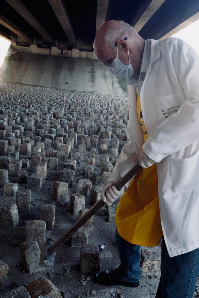 Derrubando as pedras embaixo do viaduto a marretadas