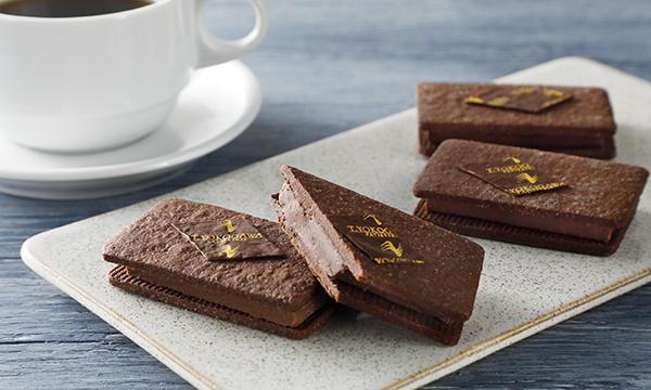 【今売れてます】可愛らしいパッケージ&個包装のチョコレートスイーツ♪キャラメリゼしたアーモンド&ヘーゼルナッツをチョコレートと混ぜ合わせ、サクサク食感のクッキーでサンドした一品!お手頃なので、自分チョコにもおすすめです。⇒ #接待の手土産 #取り寄せOK