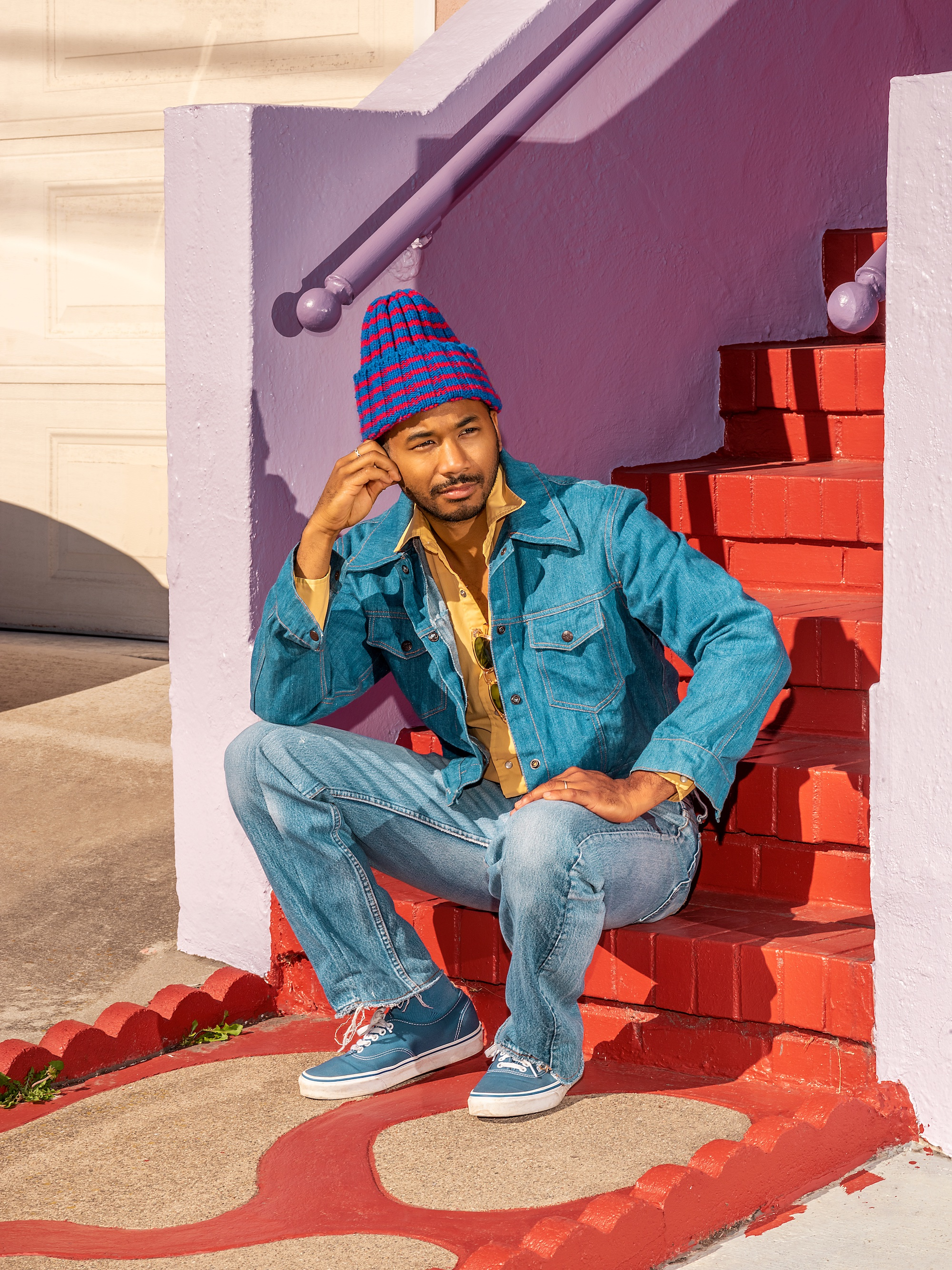UofSC alum Chaz Bundick is posed sitting on a colorful staircase. He is wearing a beanie and a jean jacket.