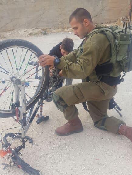إسرائيل تغرد : بارك الله في يد امتدت لترسم السعادة على وجه أحد الاطفال. الصورة لجندي إسرائيلي يساعد طفلا فلسطينيا ف…
