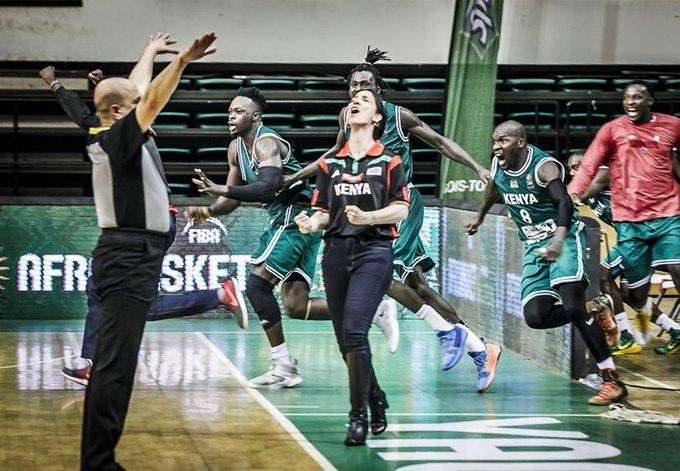 L'arbitre lève les bras pour terminer le match, tandis que les joueurs et la coach sautent de joie.