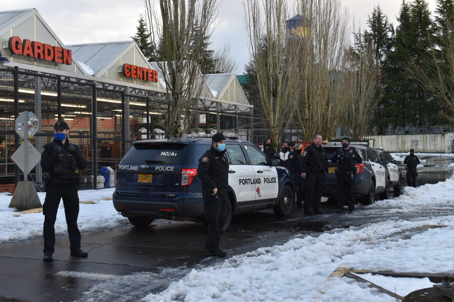 line of three police cruisers marked Portland Police with 7 or eight officers and a few non uniformed individals standing in the snow in a parking lot at a fred meyer. to the left you can see the garden center of the store with its red letters and greenhouse roof. the dumpsters are back in the distance, not really visible through the trees