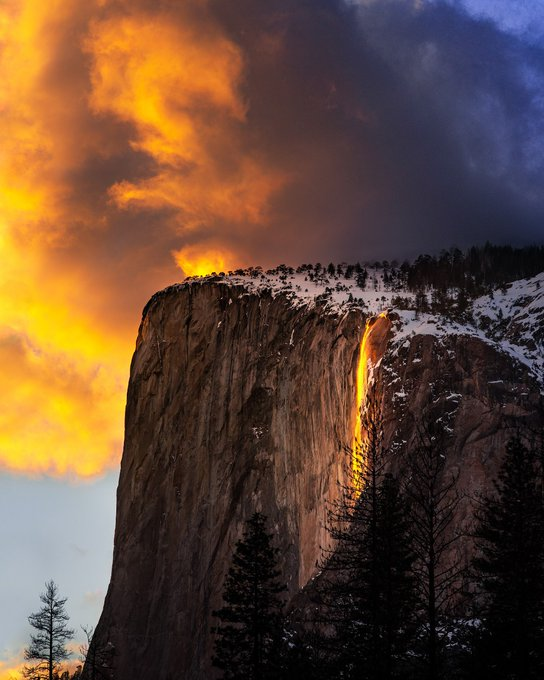 Orange light comes from waterfall in between two snow covered cliffs.