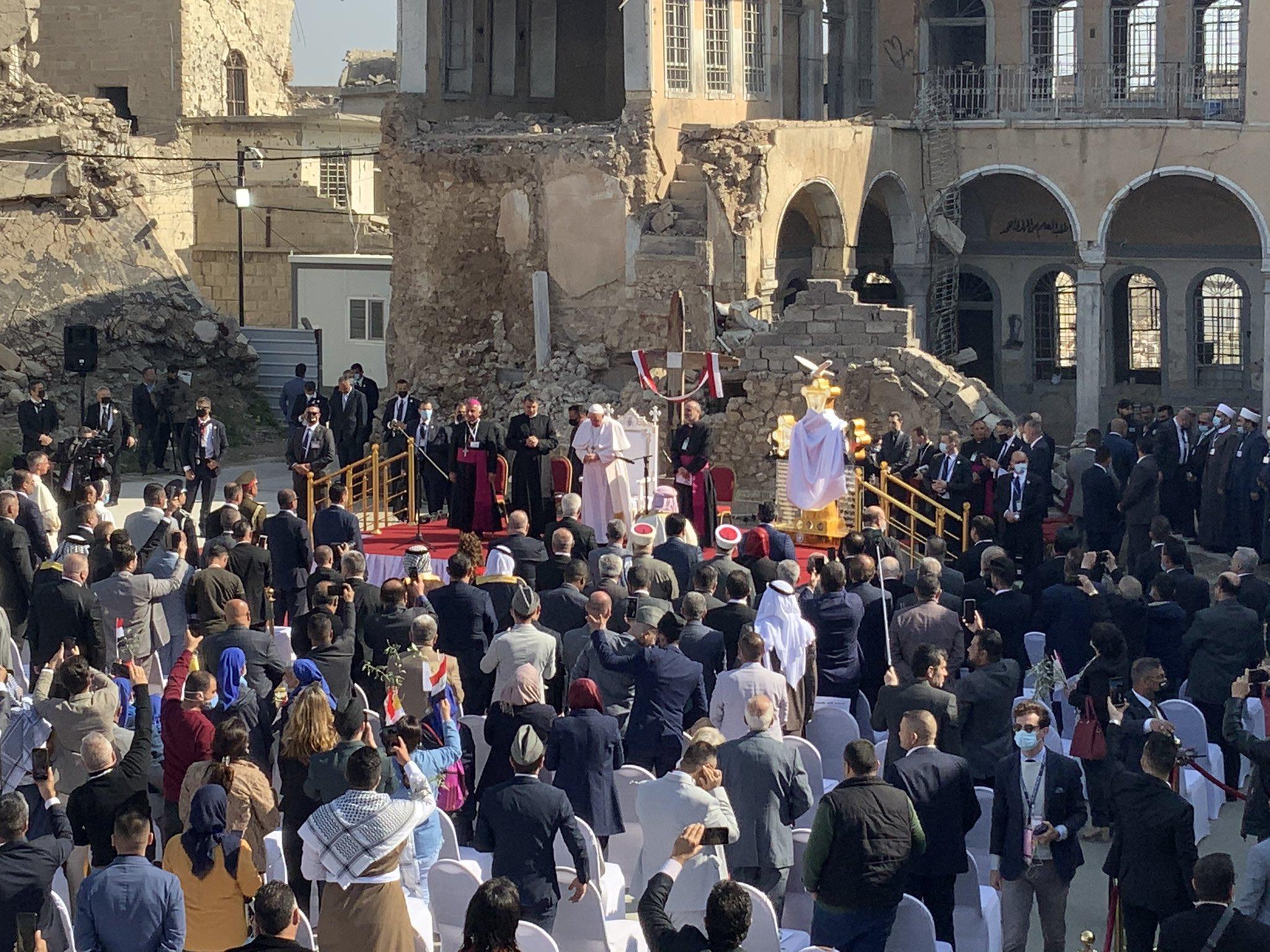 Francisco ora delante de las ruinas de Mosul
