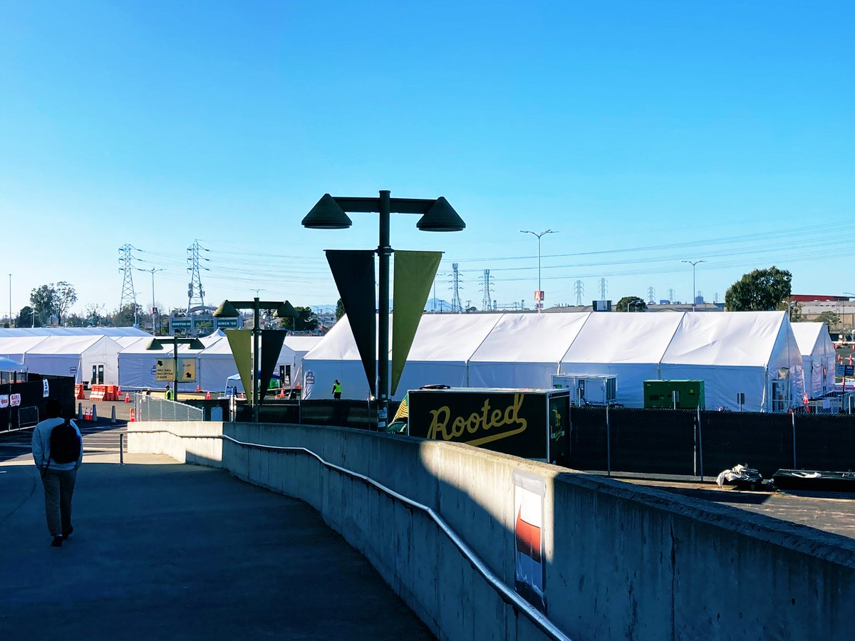 Past the FEMA checkpoint and at the end of the ramp/walkway: white tents staffed by the US Coast Guard. In one tent, you check in. In a 2nd tent, you get the vaccine. In a 3rd tent, you wait to see if you'll have a reaction to the vaccine. Then you can go. #CovidVaccine #Oakland
