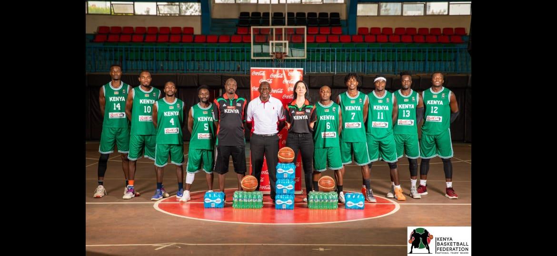 Les joueurs de l'équipe kényane de basket posent en V, arrangés par taille, dans leurs maillots et shorts verts.